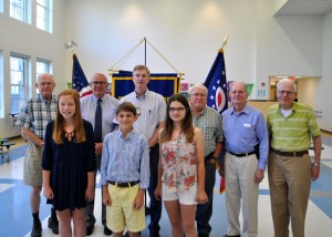 The essay winners stand with the Kiwanis members who have served our country.  Left to right (top): Roger Stafford, Jim Downing, Mike Pope, Jim Gilchrist, Don Keyes, Dick Wendel Left to right (bottom): Olivia Simpson, Trip Fries, Ally Scheeser (not pictured: Ellese Lowery)