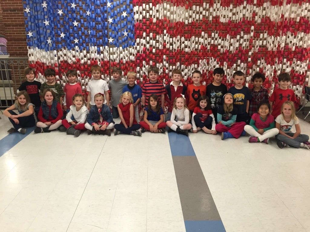 "Mariemont Elementary 1st grade students sit in front of the ""flag"" they created."